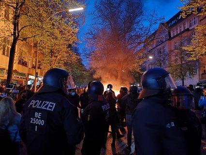 Polizisten sichern die brennenden Barrikaden.