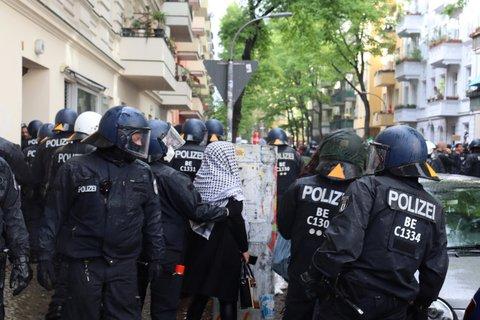 Die Polizei versucht die Friedelstraße zu räumen, in der sie zuvor mit Steinen beworfen wurde.