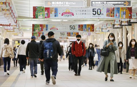 Menschen mit Masken laufen durch die Stadt. Die japanische Regierung wird ab dem 16. Mai neben den Präfekturen Hiroshima und Okayama auch Hokkaido in den laufenden Coronavirus-Notstand aufnehmen.