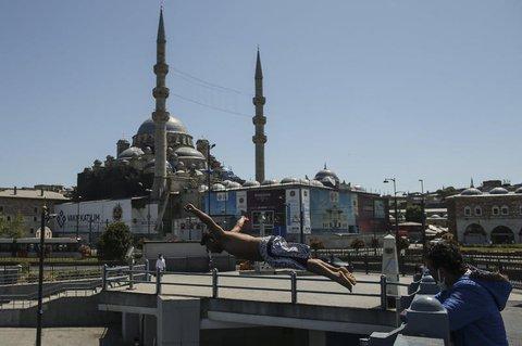 Vor dem Hintergrund der historischen Neuen Moschee springt ein Jugendlicher von der Galata Brücke in den Bosporus.