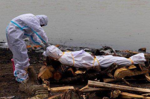 Ein Mann in einem Schutzanzug berührt den Körper seines Verwandten, der am Coronavirus gestorben ist, vor seiner Einäscherung am Ufer des Ganges in Indien, am 6. Mai. 2021.