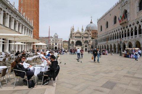 Die Menschen sitzen an Tischen im Freien am Markusplatz, während Italien die Quarantänebeschränkungen für Reisende aus Ländern der Europäischen Union, Großbritannien und Israel aufhebt und Corona-freie Flüge anbietet, um die Tourismusbranche in Venedig, Italien, wiederzubeleben.