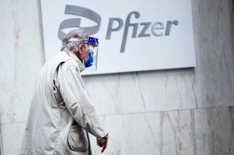 Ein Mann mit Gesichtsmaske und Schild im Pfizer-Hauptquartier in New York.