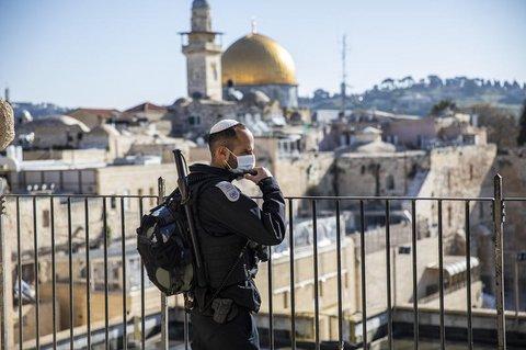 Ein israelischer Polizist mit Mundschutz steht in der Altstadt Wache, im  Hintergrund der Felsendom auf demTempelberg.