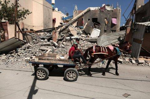 Zwei Männer vor einem zerstörten Haus im Gazastreifen.