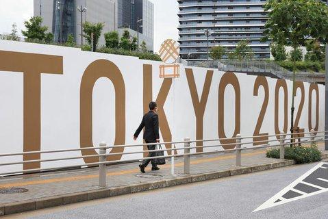 Ein Mann geht vor der Baustelle des neuen Nationalstadions an einer Absperrung mit der Aufschrift «TOKYO 2020» entlang.