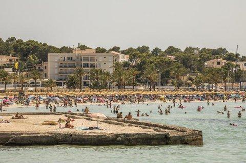 Touristen am Strand von Arenal auf Mallorca.