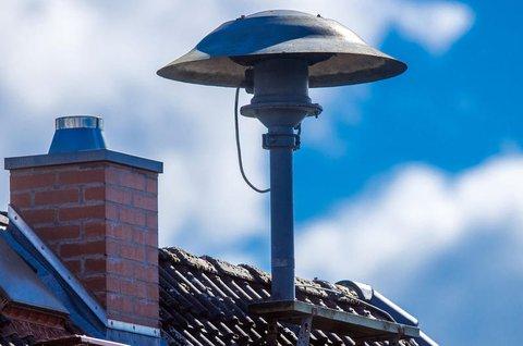 Eine Alarmsirene steht auf einem Hausdach.