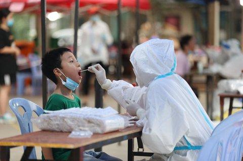 Ein medizinischer Angestellter entnimmt einem Kind eine Abstrichprobe für einen Corona-Nukleinsäuretest in einem Testzentrum im Distrikt Siming.