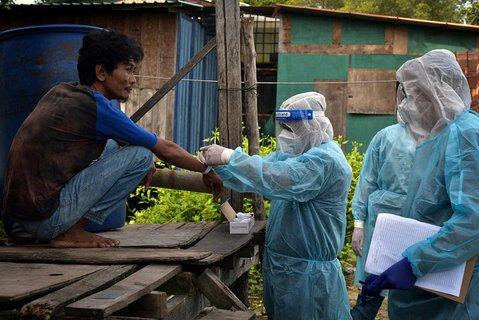 Einem Mann wird in Labuan ein Quarantäne-Armband angelegt. Dies soll helfen, die Pandemie einzudämmen.