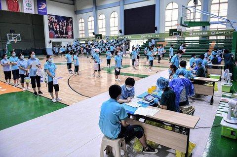 Schüler, die sich an einer High School in Shenyang in der nordöstlichen chinesischen Provinz Liaoning anstellen, um den Sinopharm Covid-19-Impfstoff zu erhalten.