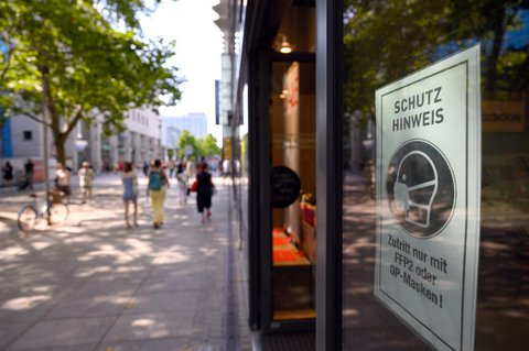 Ein Schild mit dem Hinweis auf die Maskenpflicht klebt am Schaufenster. (Symbolbild)