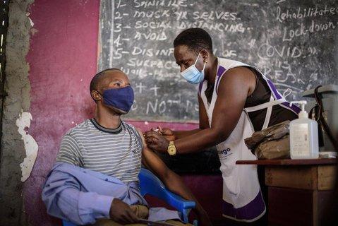 Eine Krankenschwester verabreicht einem jungen Mann eine Impfung gegen das Coronavirus vor einer Tafel mit Tipps zum Schutz vor einer Ansteckung mit dem Coronavirus im Kisenyi Health Center in der Innenstadt von Uganda.