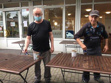Horst Krisch und Dieter Hertel lasieren die Holztische vor dem Bürgerzentrum Neukölln.