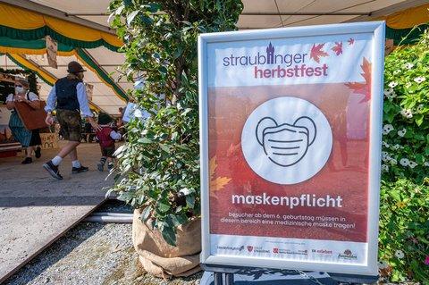 Ein Schild weist auf dem Straubinger Herbstfest auf die Maskenpflicht hin.