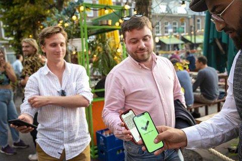 Ein Gast zeigt einem Mitarbeiter in Amsterdam sein Smartphone mit dem Corona-Pass.