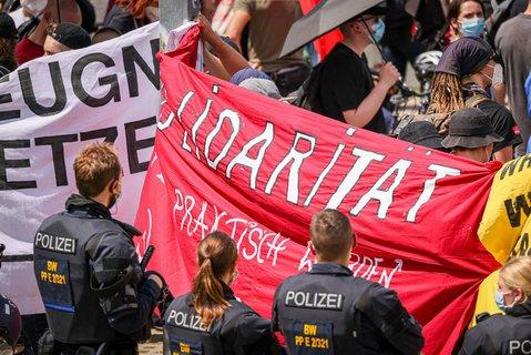"""Polizeibeamte beobachten im Juni in Karlsruhe eine Demonstration der  """"Querdenker""""-Szene."""